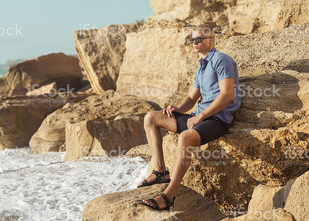 Fashionable young muscular guy resting on a rocky beach. royalty-free stock photo