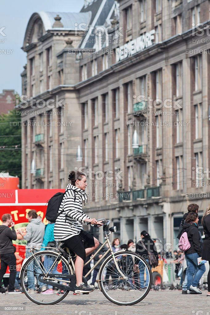 Fashionable young woman cycling on Amsterdam Dam Square stock photo