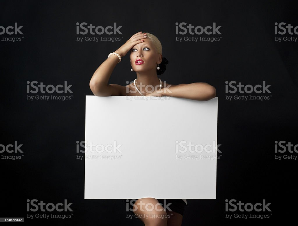Fashionable young woman holding a blank white sign royalty-free stock photo