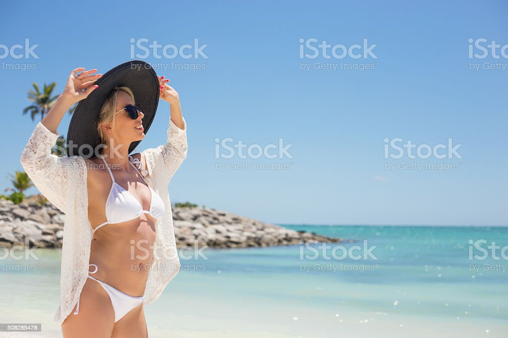 Fashionable young woman on the beach stock photo