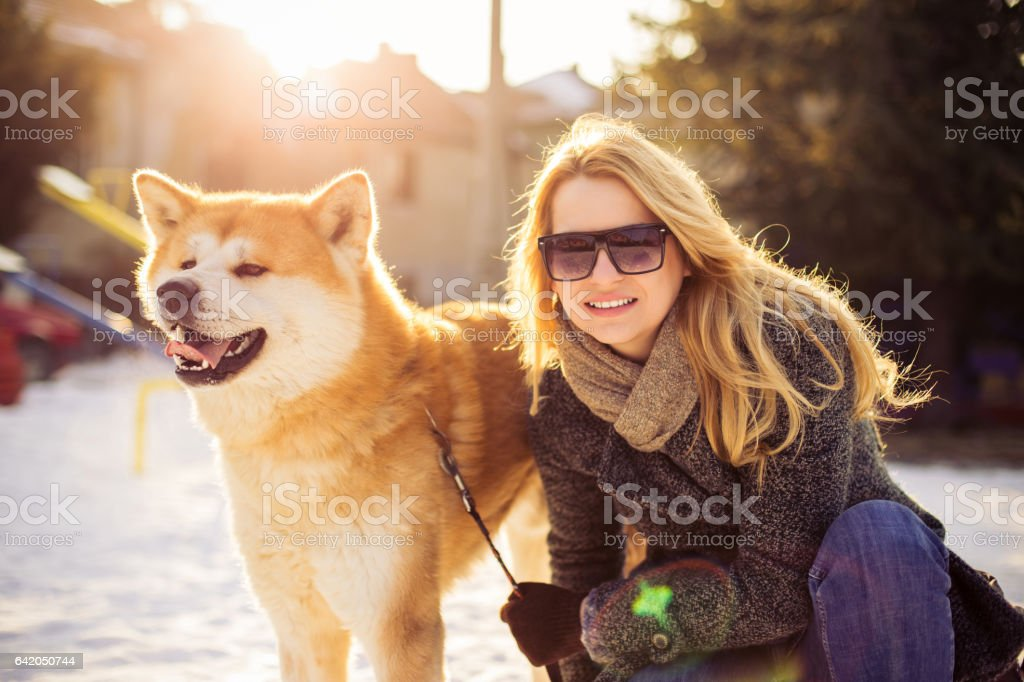Fashioned woman kneel near her dog stock photo