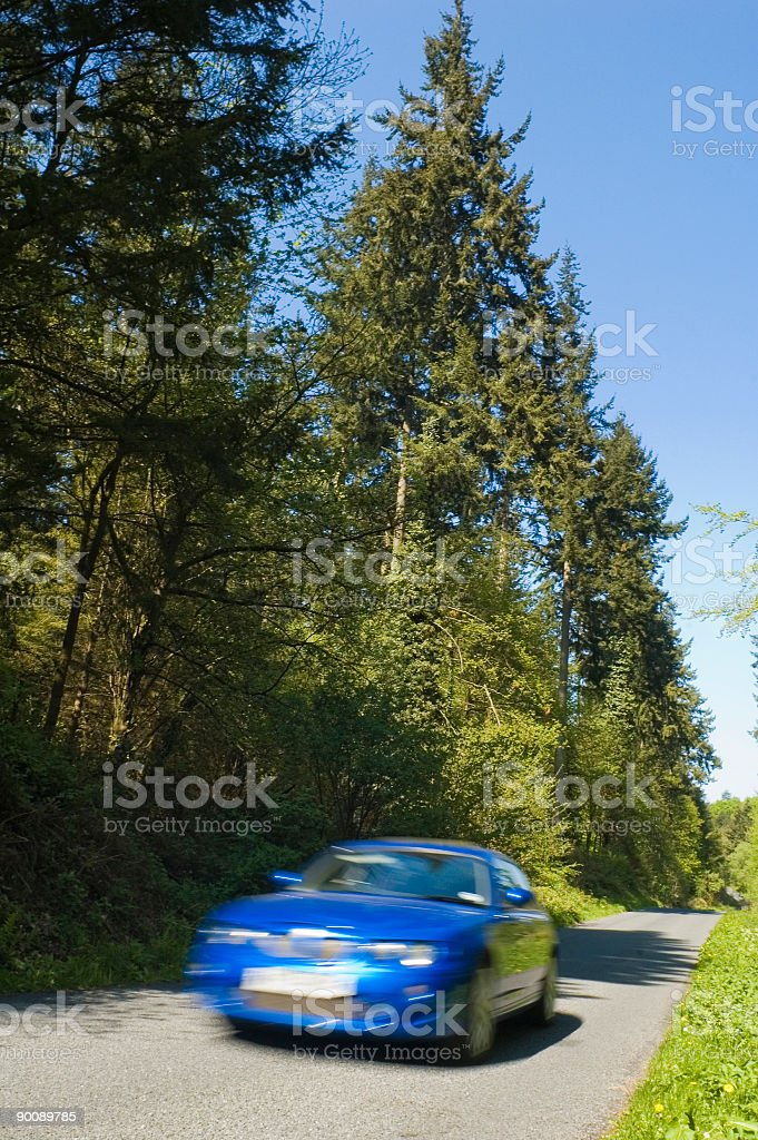 Fast car, green forest, blue sky royalty-free stock photo
