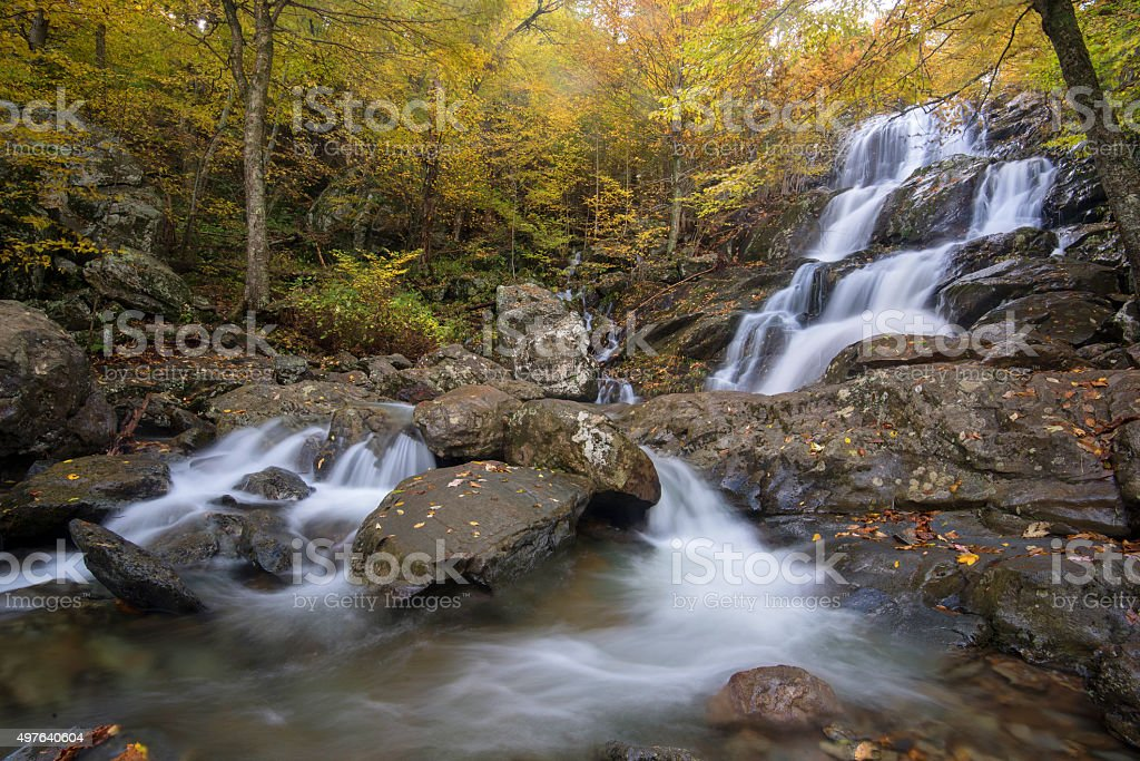 Fast flowing waterfall in Autumn leaves stock photo