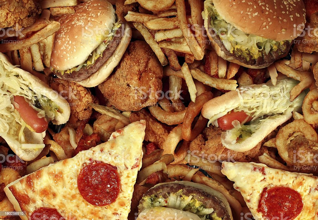 Fast food items like hot dogs, hamburgers, fries and pizza stock photo