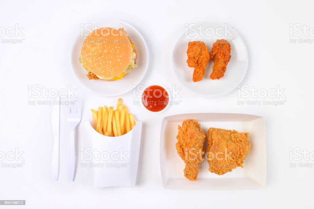 Fast food set containing burgers, fried chicken and french fries isolated on white background. stock photo