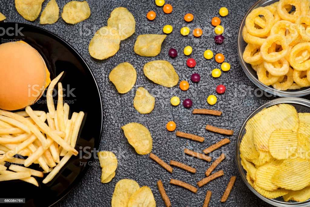 Fast food: top view of burger, french fries, chips, rings and candies. Unhealthy eating concept stock photo