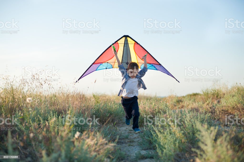 fast little boy runs across the field with a kite in his hands over his head stock photo