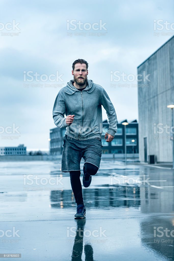 Fast male runner runs outside in the rain stock photo