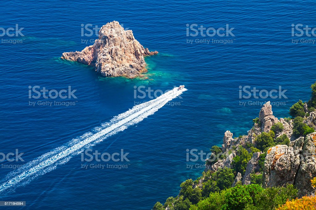 Fast motor boat goes between the stones stock photo