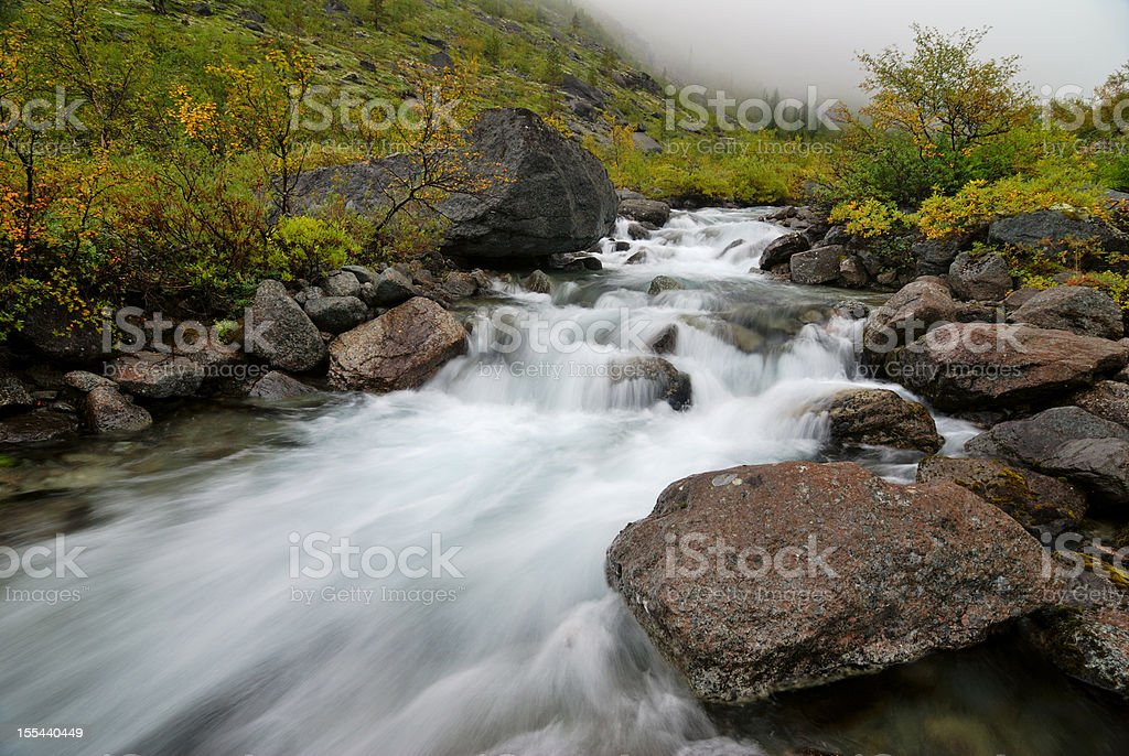 Fast mountain stream in Khibiny Mountains stock photo