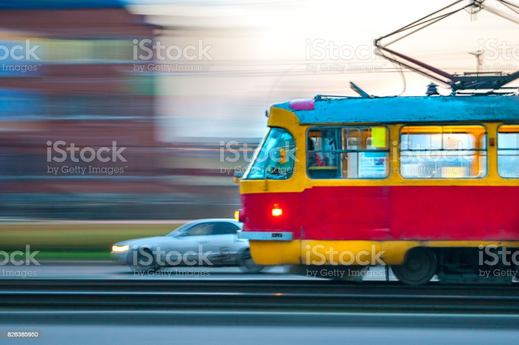 Fast moving red and yellow tram in the city with light on, panning blurry effect stock photo