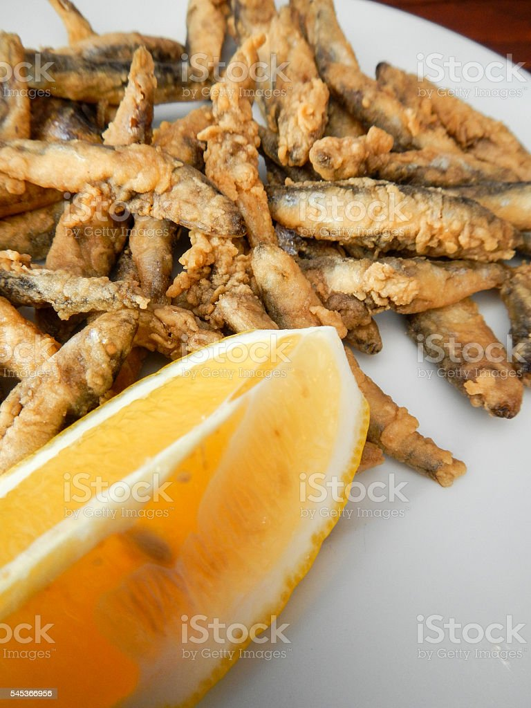 fast snack of fried small fish anchovy hamsii with lemon stock photo