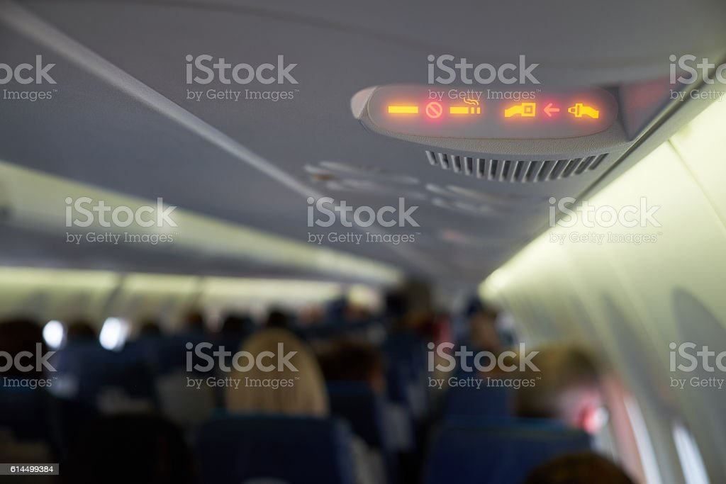 Fasten seat belts and no smoking signs in plane stock photo