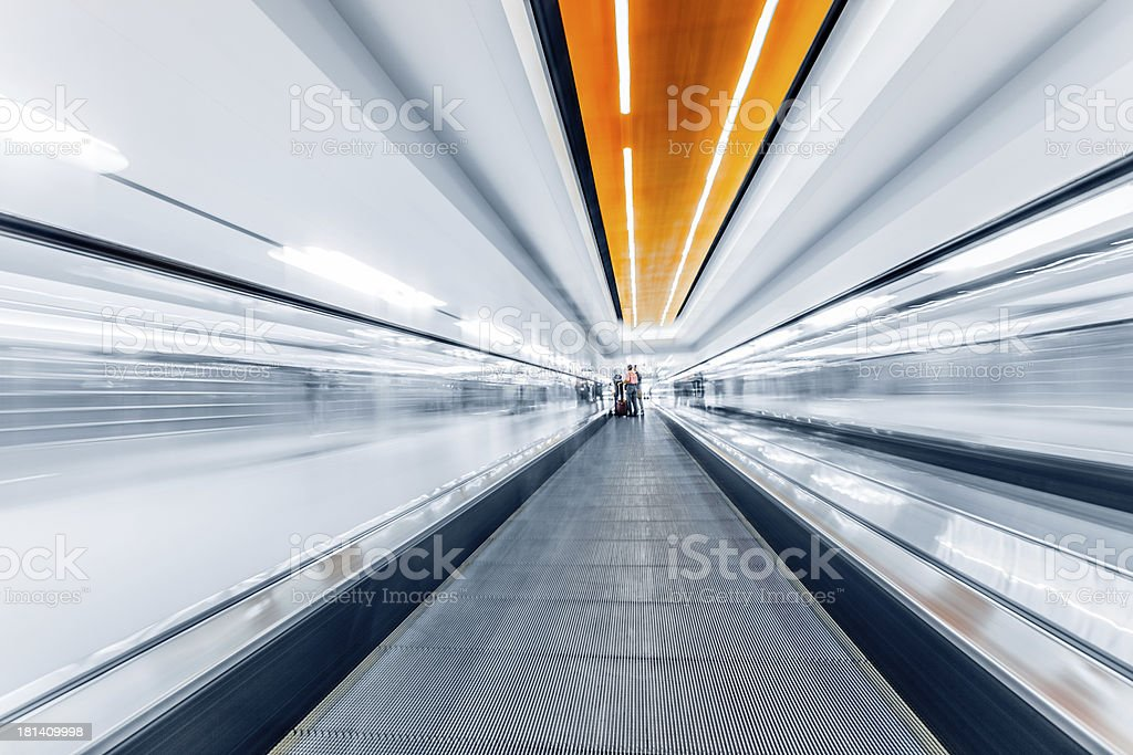 A fast-moving walkway with people in the far distance royalty-free stock photo