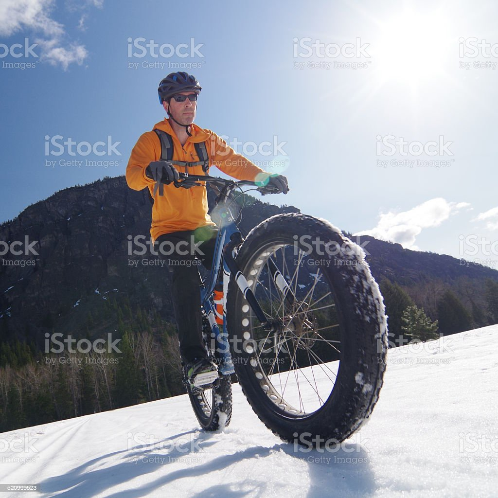 Fat bike rider on snow, highlighting big tire stock photo