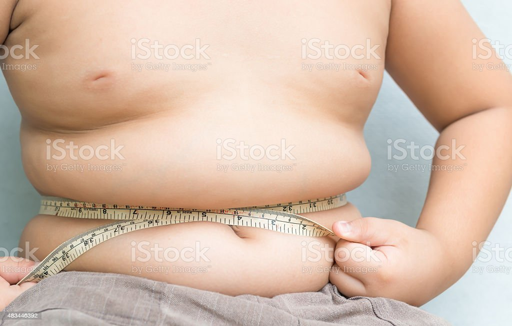 Fat boy measuring his belly with measurement tape stock photo