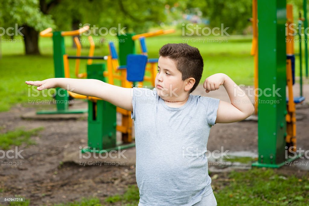 fat boy shows his muscles in background of exercise equipment stock photo