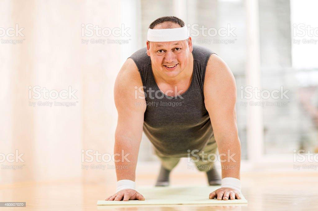 Fat man doing pushups and looking at camera. stock photo