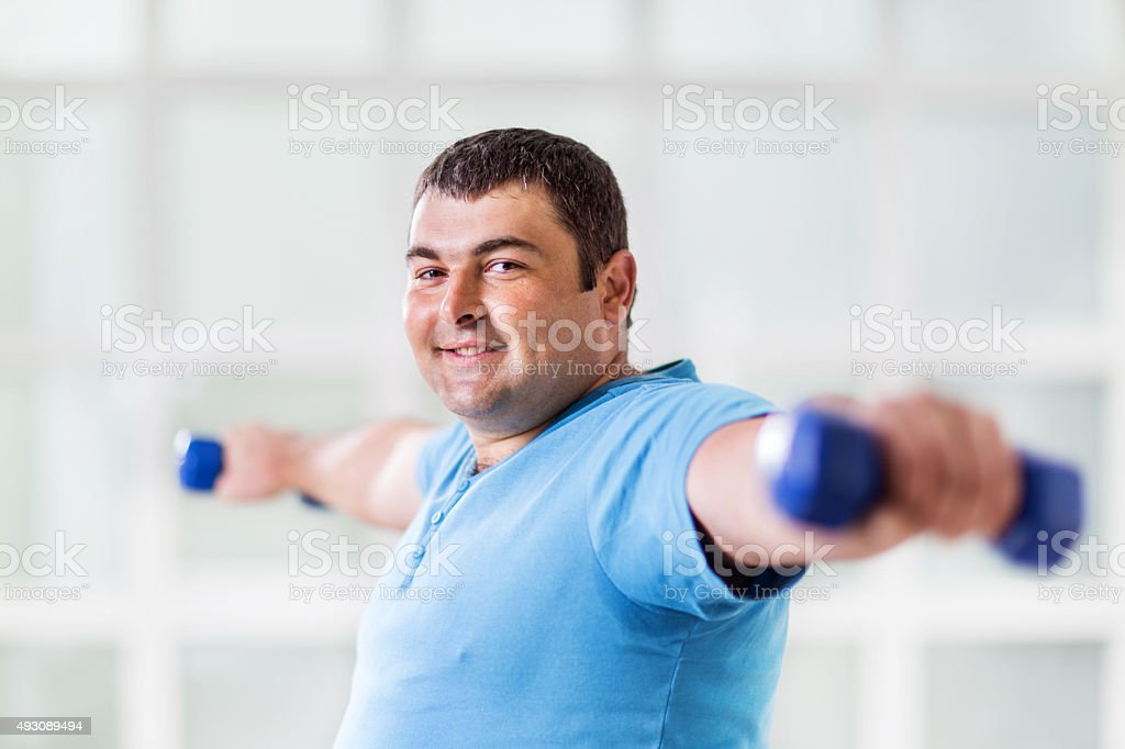 Fat man exercising with dumbbells and looking at camera. stock photo