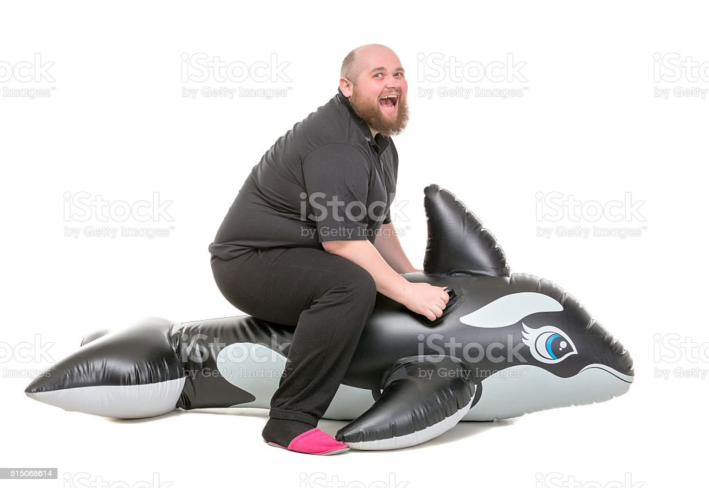 Fat Man Fun Jumping on an Inflatable Dolphin stock photo