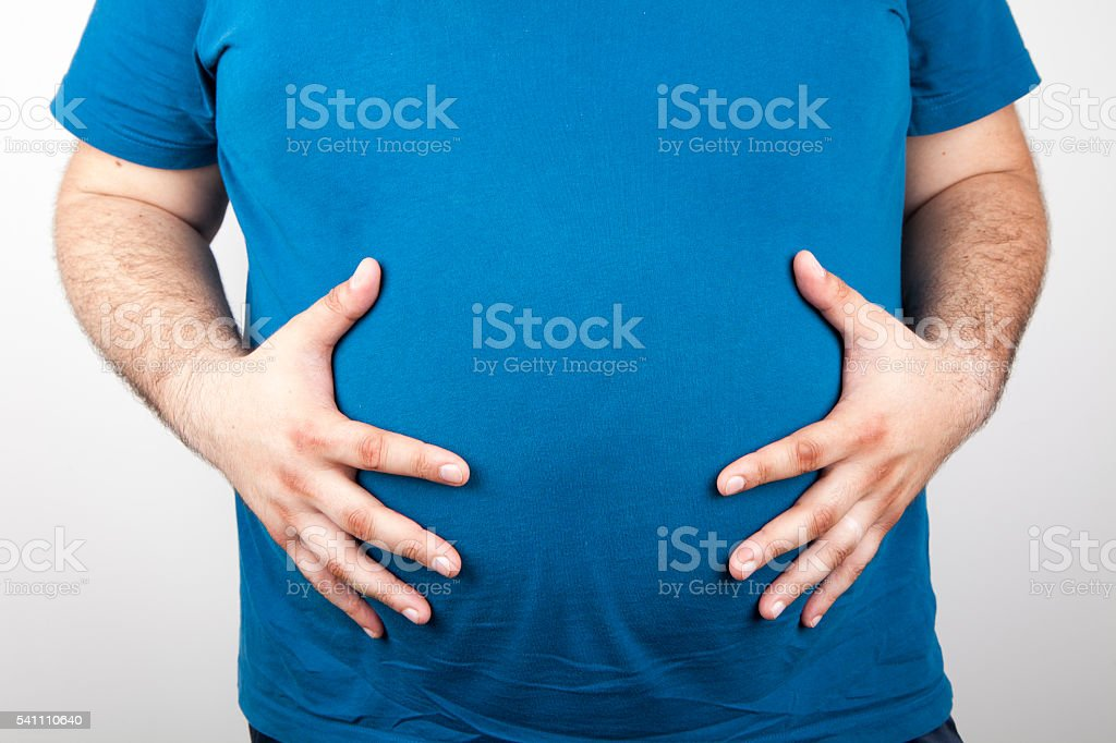 Fat man holding his stomach stock photo