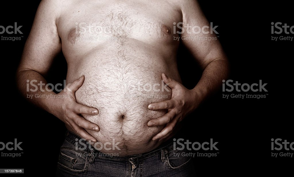 Fat man holding his stomach with jeans royalty-free stock photo