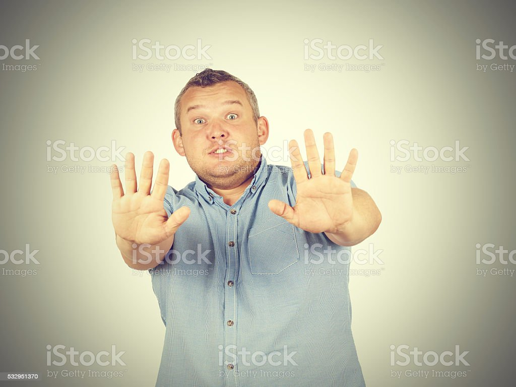 Fat man looking shocked scared trying to protect himself stock photo