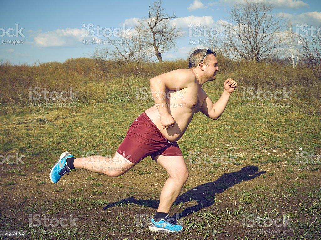 Fat man running outdoors on nature. stock photo