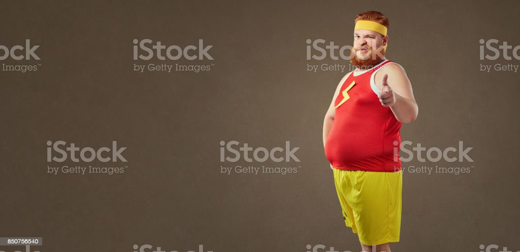 A fat man with a beard in a tracksuit. stock photo