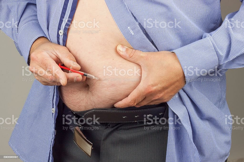 Fat man with syringe making insulin injection stock photo