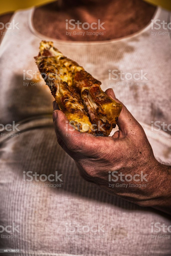 Fat old white man holding a slice of pepperoni pizza stock photo