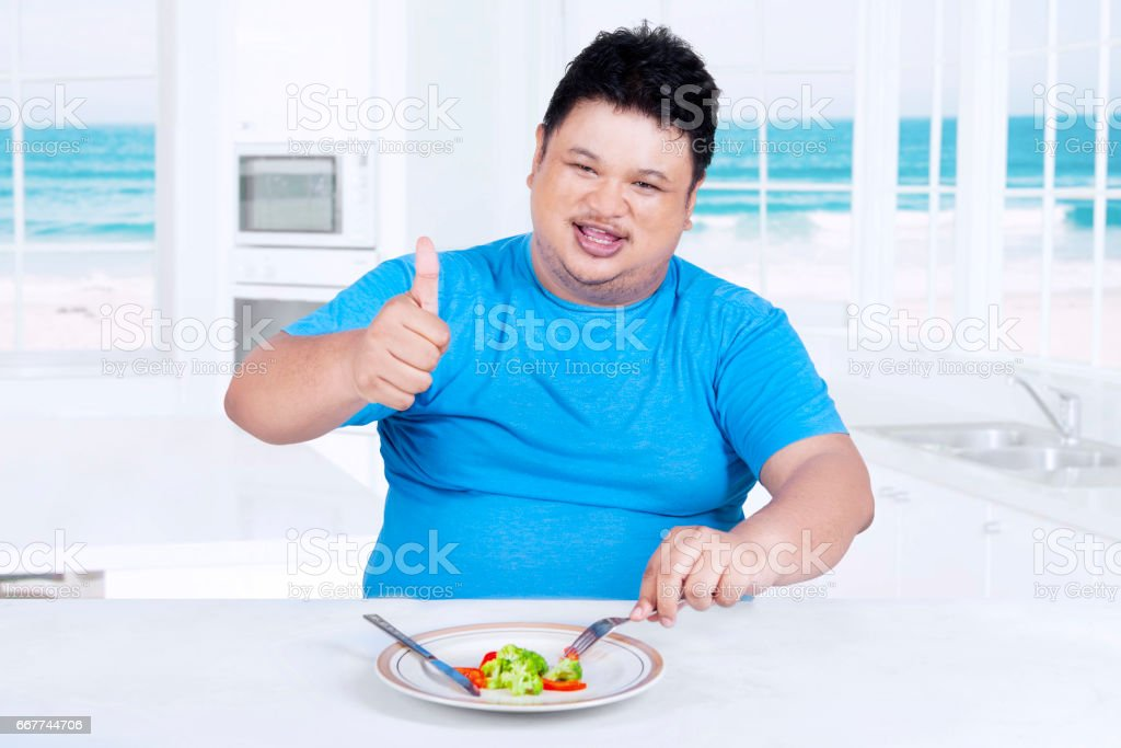 Fat person shows thumb up in the kitchen stock photo