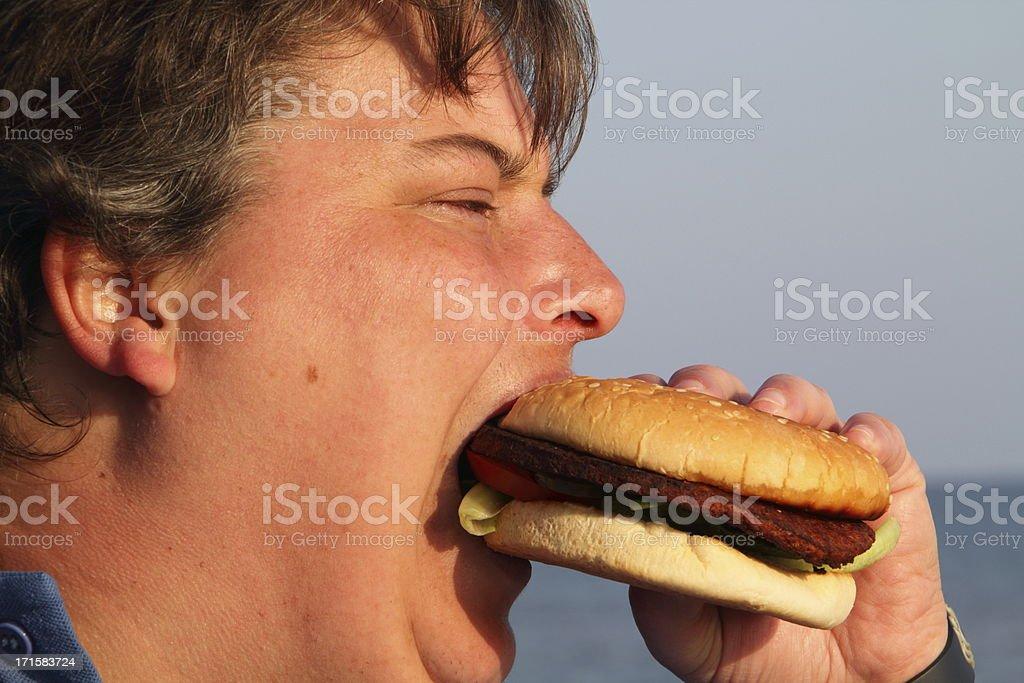 fat woman eating hamburger royalty-free stock photo