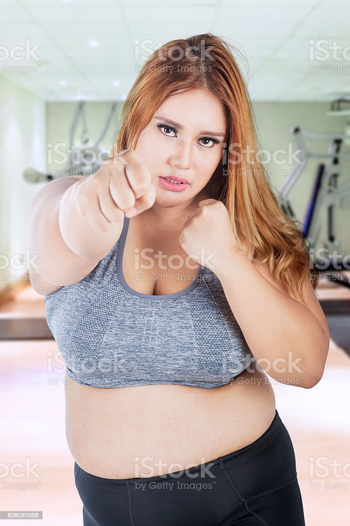 Fat woman punching in fitness center stock photo