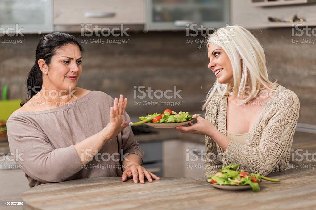 Fat woman refusing healthy salad form her friend. stock photo