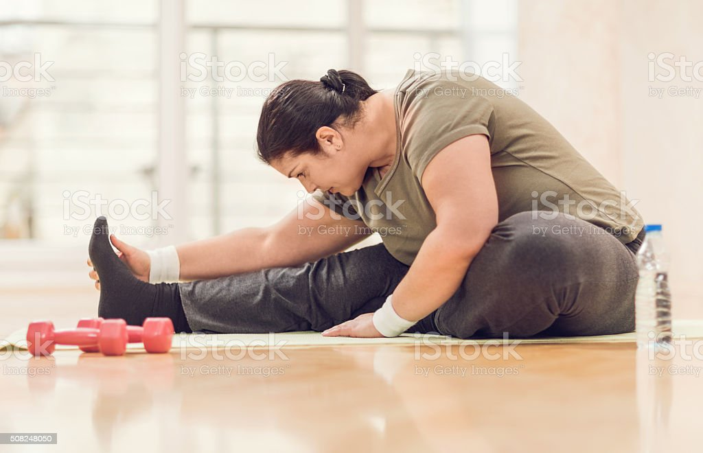 Fat woman stretching on the floor. stock photo