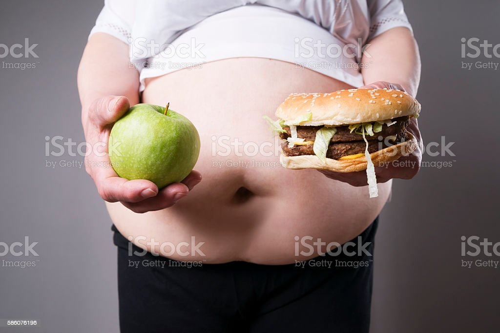 Fat women suffer from obesity with hamburger and apple stock photo