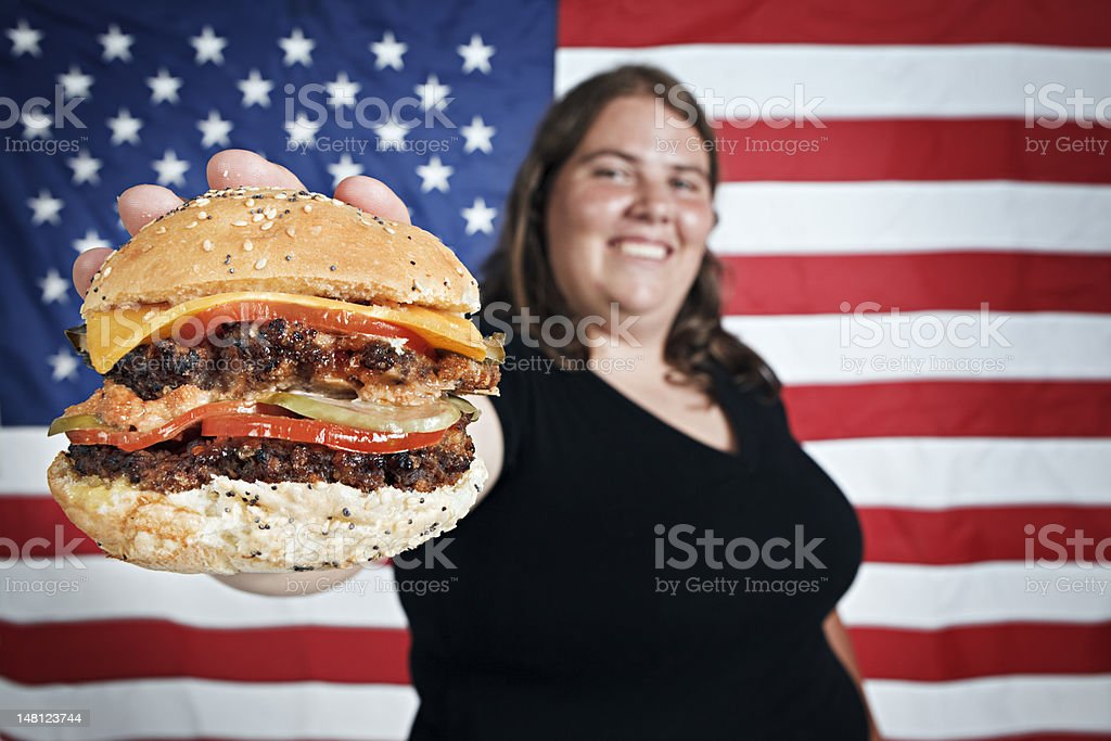 Fat young woman smilingly offers burger against US flag stock photo