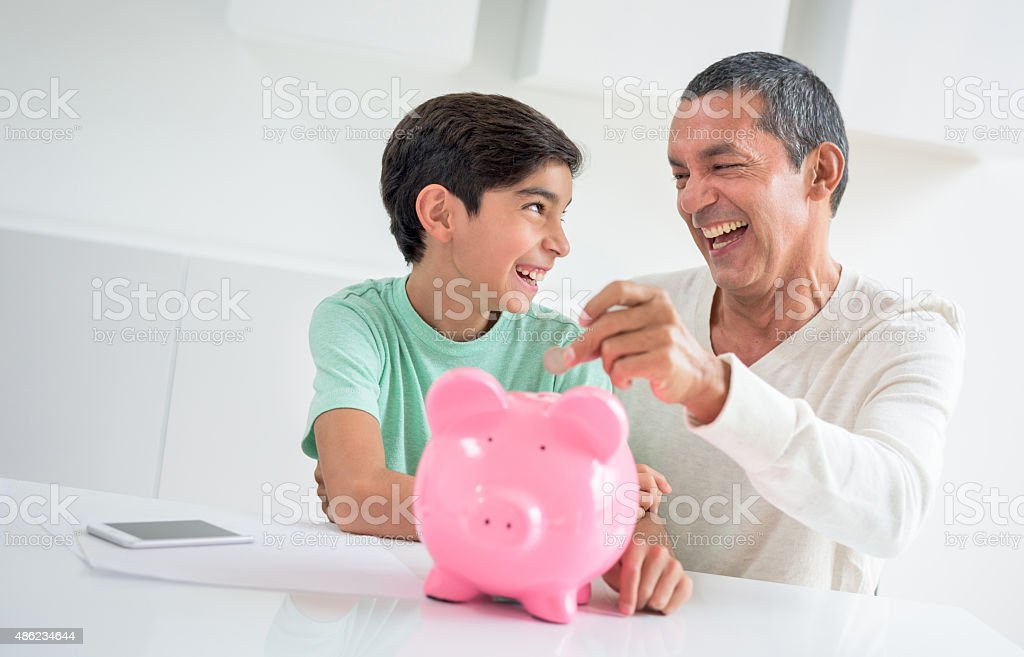 Father adding coins to his son's savings stock photo