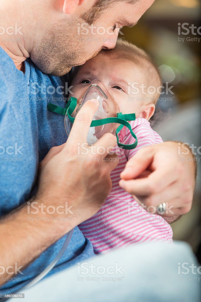 Father admistering breathing treatment to infant daughter with cystic fibrosis stock photo