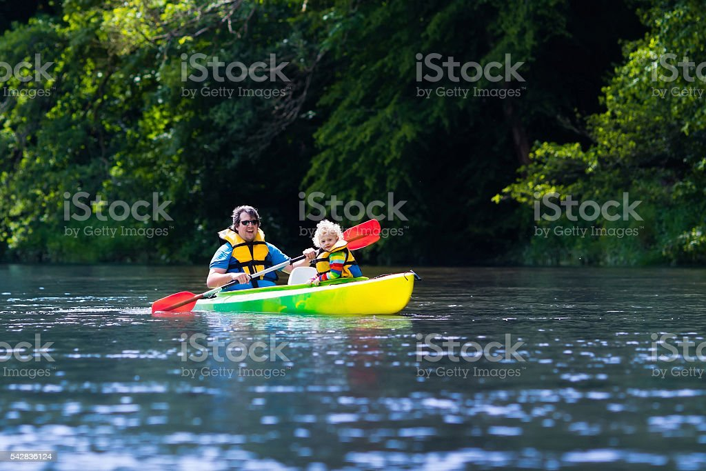 Father and adorable child kayaking in summer stock photo