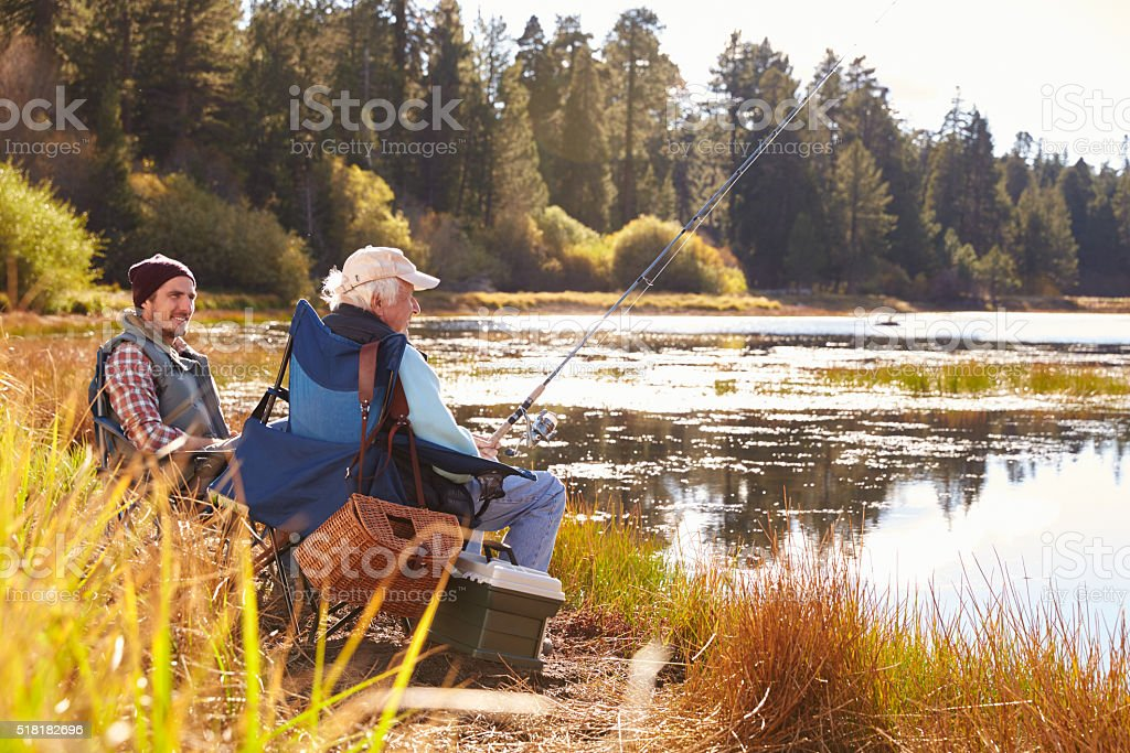Father and adult son fishing lakeside, Big Bear, California stock photo