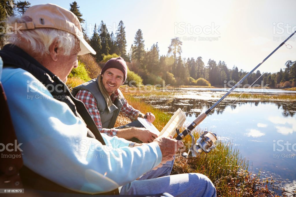 Father and adult son fishing lakeside, close-up stock photo