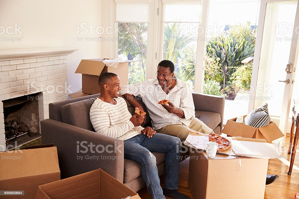 Father And Adult Son Take A Break With Pizza On Moving stock photo