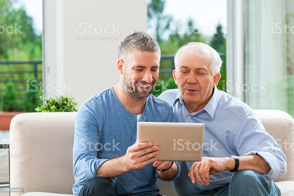 Father and adult son with digital tablet stock photo