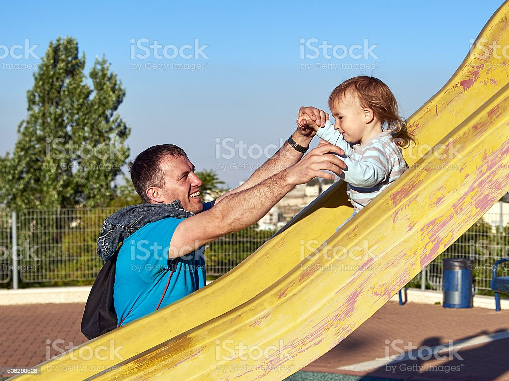 Father and baby child little boy playing on slide stock photo