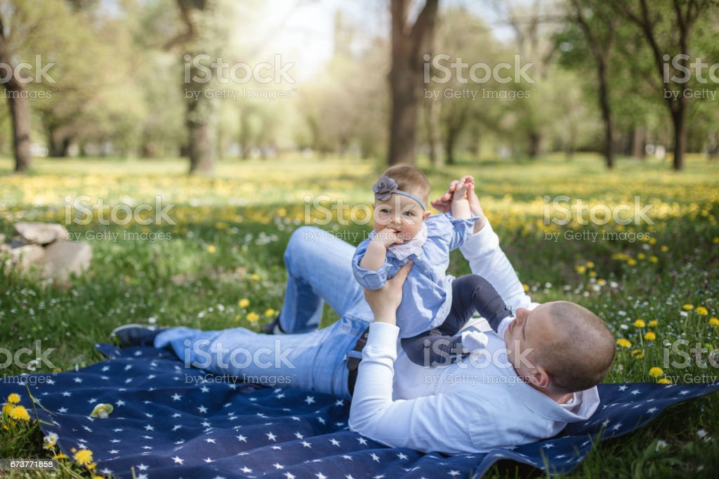 Father and baby girl rolling in the grass stock photo