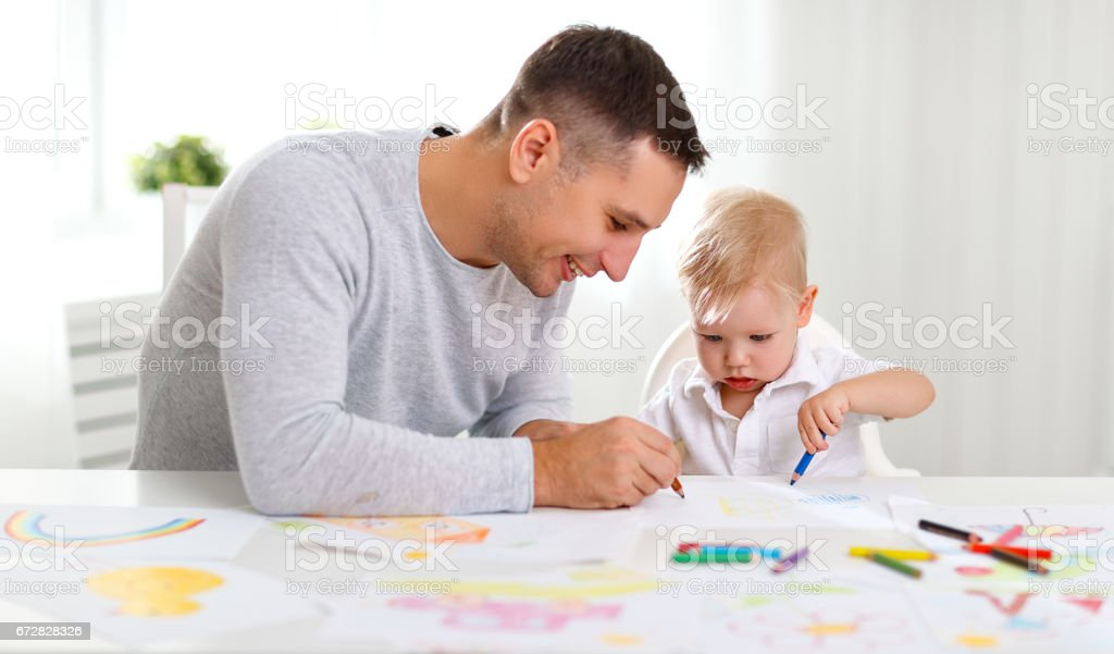 father and baby son paint together stock photo