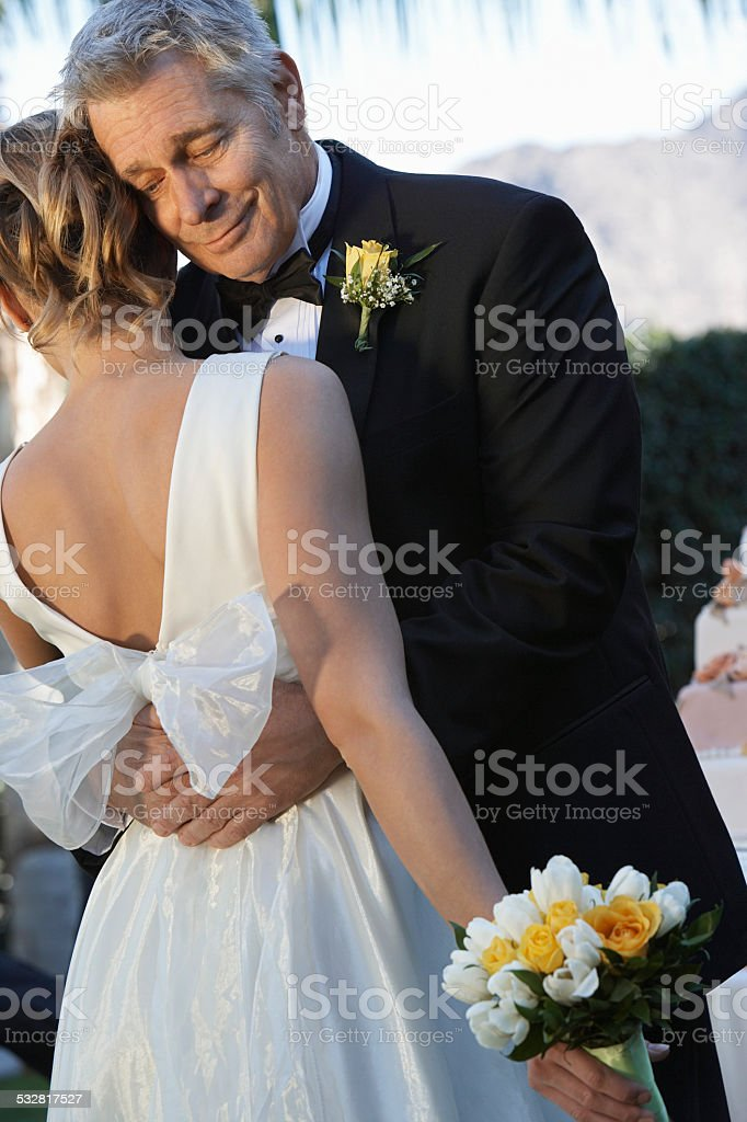 Father (facing camera) and bride dancing stock photo