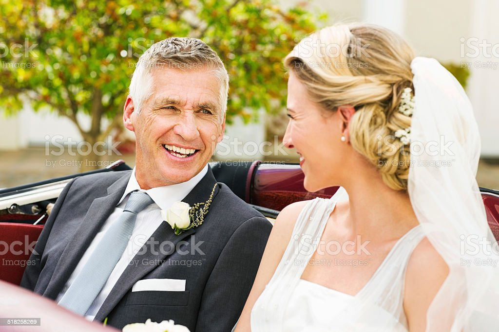Father And Bride Looking At Each While Sitting In Car stock photo